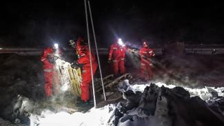scientists with headlamps on ice, cleaning up eqipment