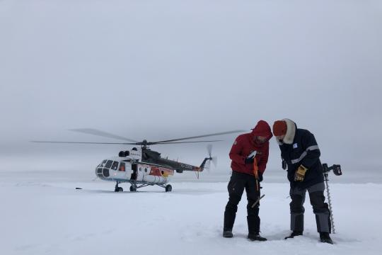 Two scientists on ice, helicopter in background