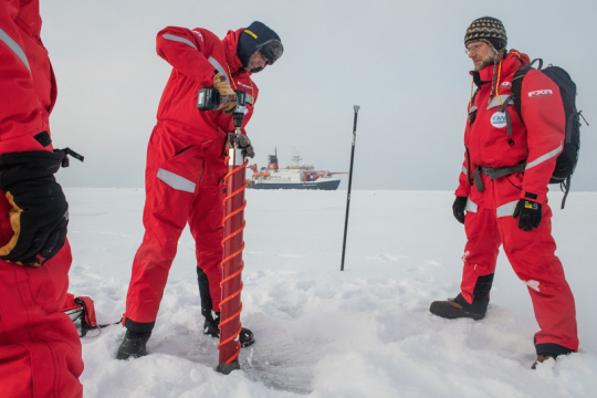 three scientists dressed in snow suits drill ice cores out on the frozen, white landscape, ship can be seen far away.