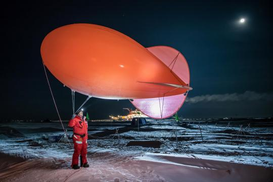 Known as Miss Piggy, the weather balloon collects data within the few thousand feet of atmosphere above the ice. Graeser wears a red snowsuit, and the ship Polarstern is visible in the distance. December 12, 2019. Photo: Esther Horvath